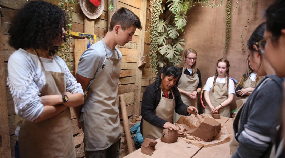 Voluntarios aprendiendo sobre el uso de barro en un taller durante su voluntariado social en Perú.